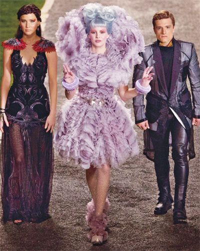 Covered head to toe in lavender frills, Effie looks over-the-top as she makes her way to the final stop on Katniss and Peeta's victory tour ...