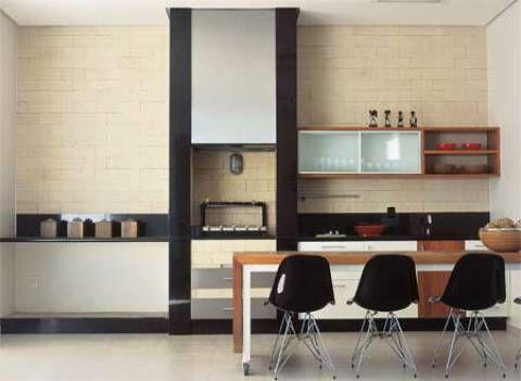 A solução para assar carnes dentro de casa foi a churrasqueira a gás (Fischer), com uma chapa de aço inox ocultando a coifa e placas de granito preto nas laterais da caixa. O projeto é dos arquitetos Sanderson Porto e Ana Paula de Castro.