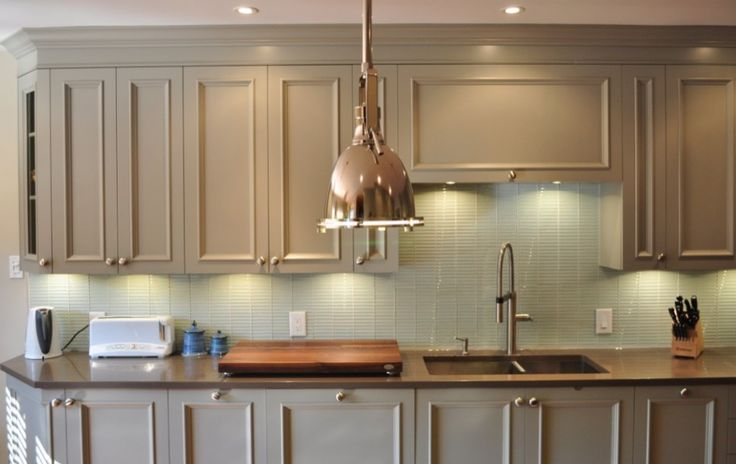 These opulent grey finished kitchen cabinets with enhanced raised panels are perfectly balanced with the chrome hanging light, grey tiled backsplash and natural wood countertop.