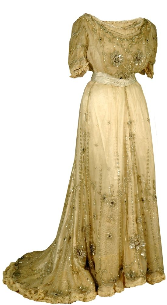 """""""Pouter Pigeon"""" Dress, Paris, France: 1907, cotton net heavily-trimmed with sequins, beads and satin.    Woven Mark: """"Denova, 32 Avenue de l'Opera, Paris.""""    """"Denova is listed in a 1907 shopping guide for women studying in Paris as offering 'evening gowns, blouses, and street dresses tailor-made . . . specially good.'"""""""