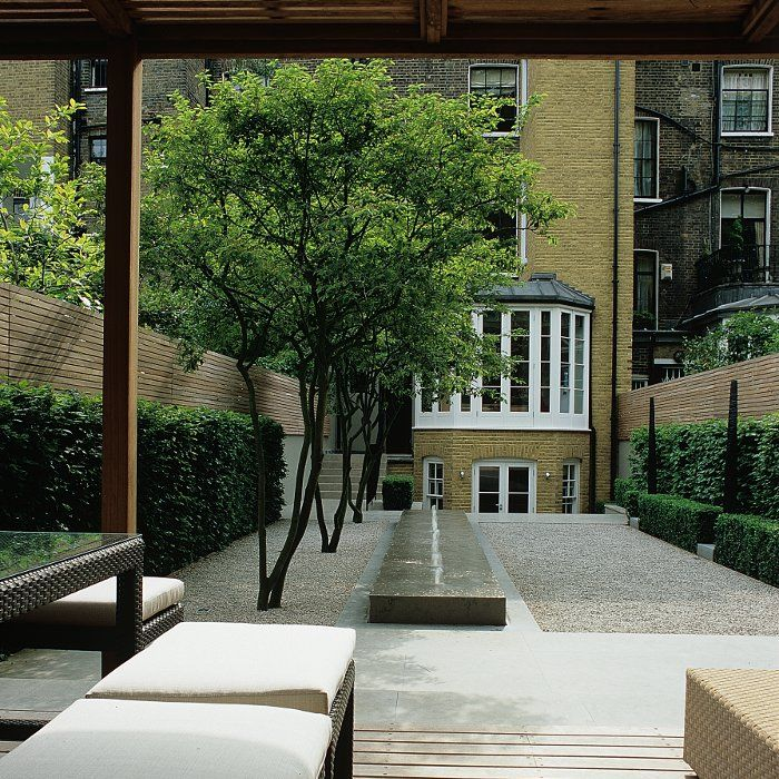 long London backyard; instead of a pool, a raised fountain. like the trees in the gravel and the art