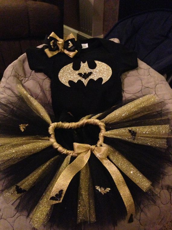 Black and Gold sparkly tutu, detailed with black and gold sparkly bats! Wrapped in gold ribbon. Eye/ear piece is black sparkly with gold glitter bats (stretchy headband attached), and matching cuffs, detailed with gold jewels and bats! Shirts are decorated with hand drawn cut gold glitter bat and name on back or front depending on size/space. For smaller sizes name will be on back, but usually sizes bigger than 6 months I can fit name on the front:) ***NOTE: For sizes 0-18 months, I will do…