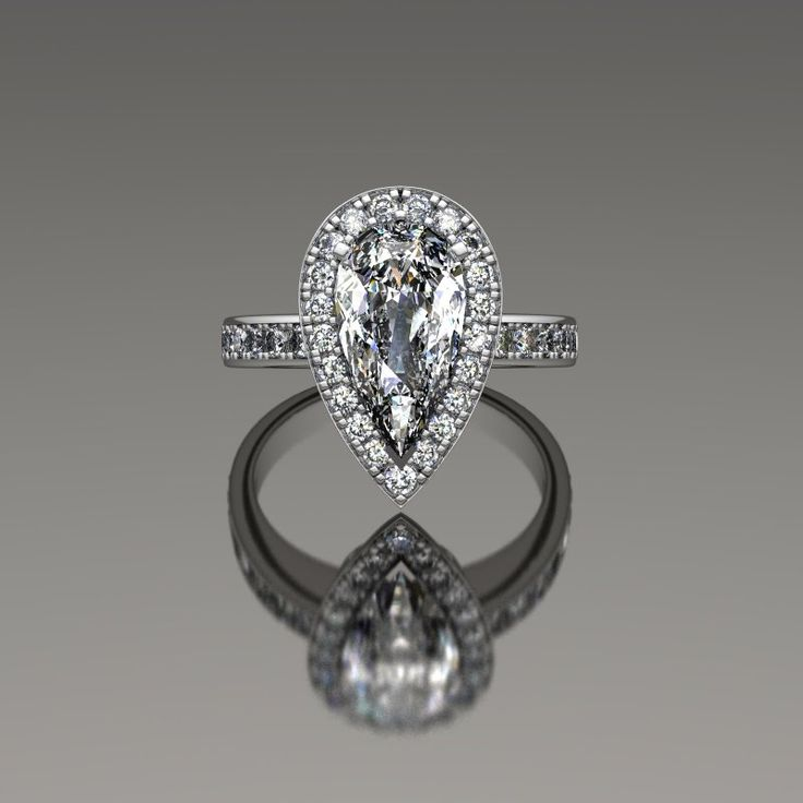 Delicate tear-drop diamond halo engagement ring.