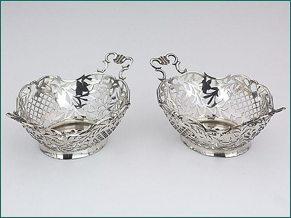 Een stel zilveren bonbonmandjes uit 1914 - Een stel Hollands zilveren bonbonmandjes  2e gehalte Afmeting 16,2 (incl. handvaten) x 10,4 x 4,8 cm Gewicht 184 gram (2) Jaarletter E = 1914 Meesterteken W.H. van Akkeren - Den Haag