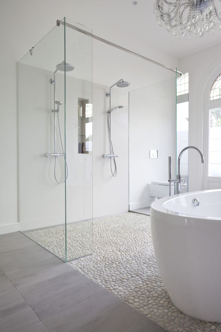Modern bathroom features a crystal chandelier, free standing acrylic tub, a mix of marble tile and pebble floor and a double shower with custom made glass panels.