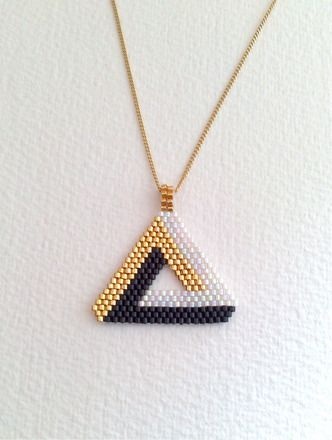 Pendentif  Triangle 3 D réalisé d'après un dessin personnel , à l'aiguille (technique du Brick stich ) .J'ai utilisé des perles Miyuki delica  noir, blanc irisé et doré .  - 18763553