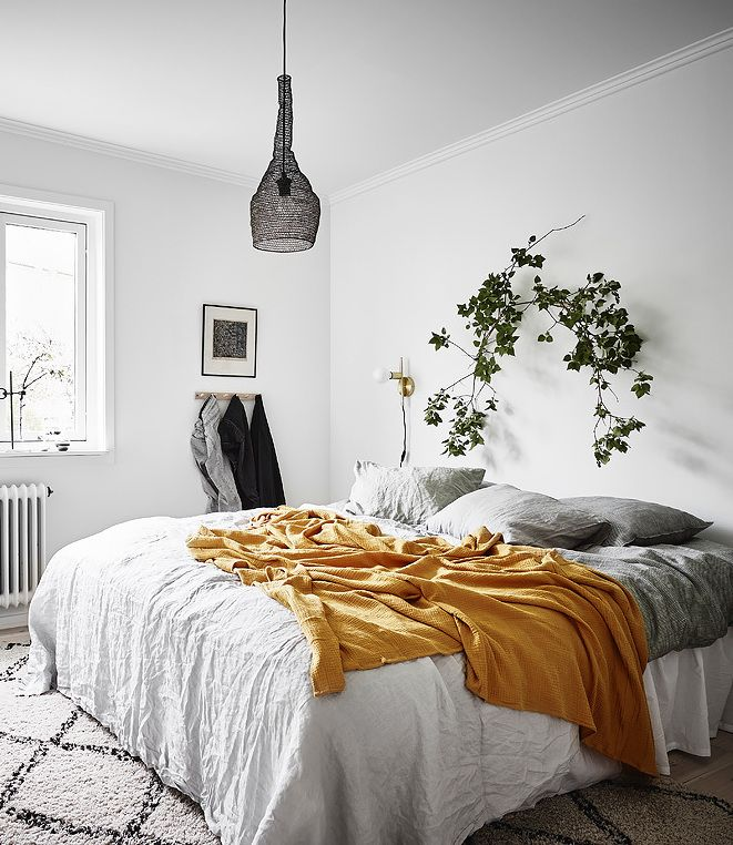White bedroom with pops of yellow throw - love the ivy on the wall