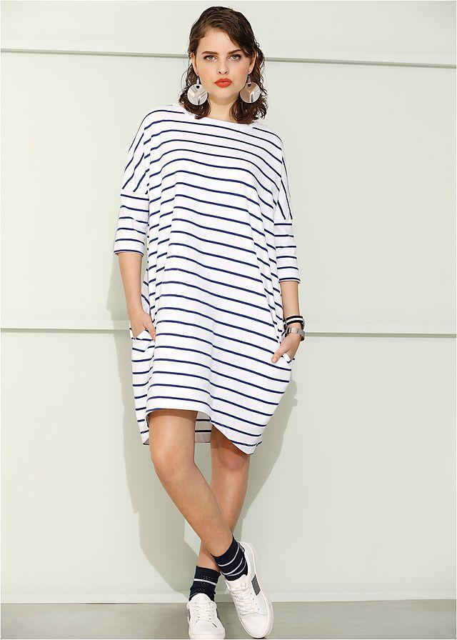 Luźniejsza sukienka dresowa w modnym fasonie o linii litery O, w atrakcyjny wzór w paski. Po bokach wpuszczane kieszenie.