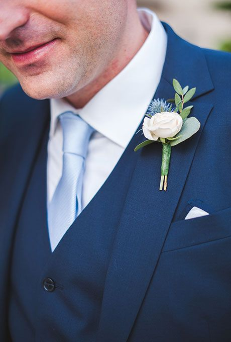 Brides.com: . A classic, mini white rose boutonniere with greenery and thistle, created by Laetitia C.