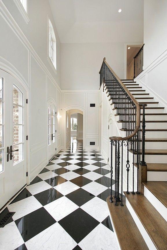 Langen, schmalen weißen Mauern Eingangshalle mit schwarz-weiß karierten Boden und Quartal Landung Treppe mit kleinen Landung auf dem Boden.