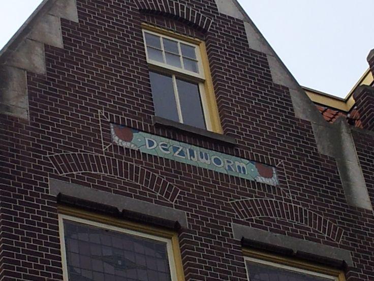 """Markt 21 - """"De Zijworm"""" - WINKELWOONHUIS, genaamd 'De zijworm', in 1903 in iets gewijzigde vorm gebouwd naar ontwerp van architect C.J.L. Kersbergen uit 1899 in de stijl van de Neo-Hollandse Renaissance. In het pand was een brood- en beschuitbakkerij gevestigd, waaraan de sectieltableaus op de zuidgevel herinneren. De hoektoren met hijsluik diende voor de aanvoer en vervolgens opslag op de zolder van bakkerijgrondstoffen als meel."""
