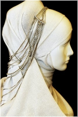A white volumized headscarf adorned with... necklaces, I think? A sophisticated look.