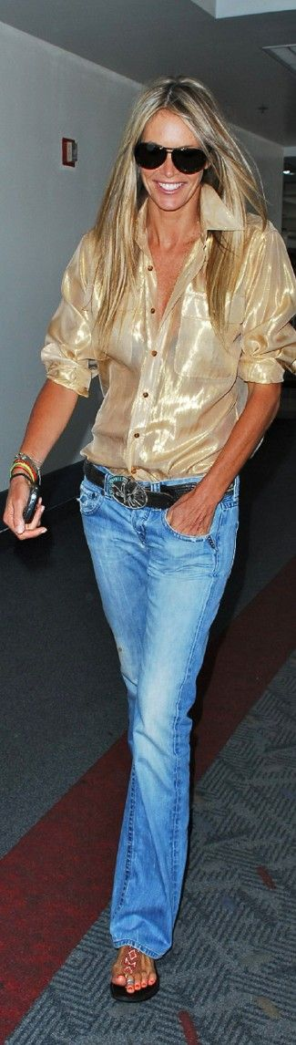 one of the original beach ladies, Elle MacPherson sporting comfy, faded jeans, a glam gold top, sandals and a tan - perfect
