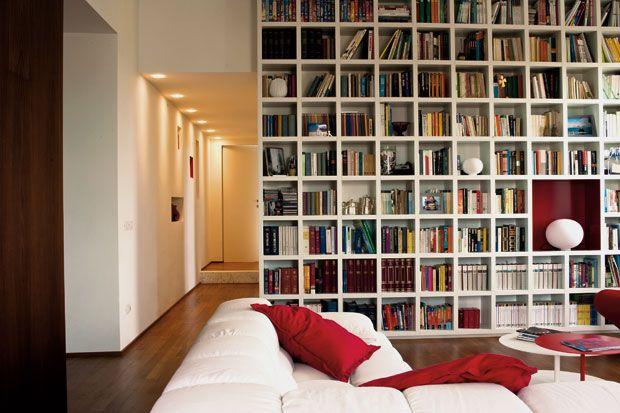 Il living, con la libreria in laccato bianco: realizzata su disegno, traccia una sorta di linea di confine fra l'area giorno e la zona notte e, sul lato del corridoio, include un vano guardaroba. Sui