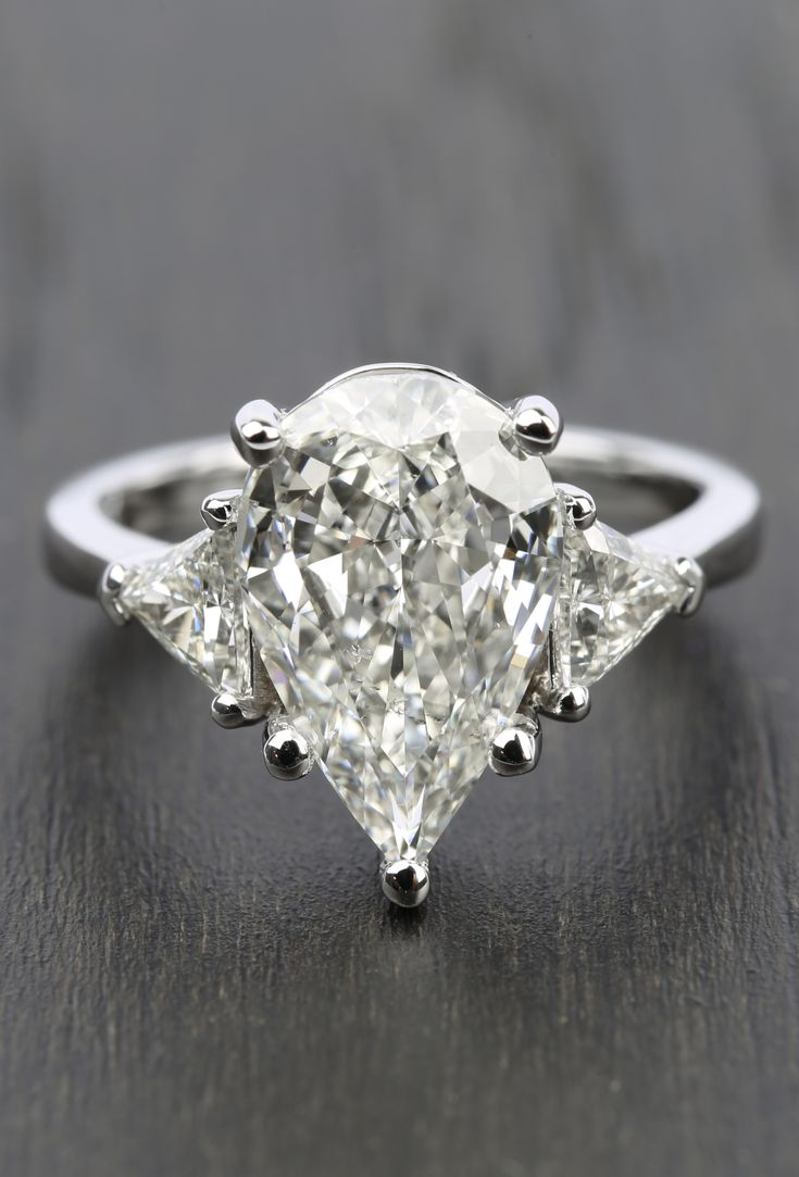 This Stunning Threestone Trillion Engagement Ring With Pear Diamond Center  Features A 311 Carat