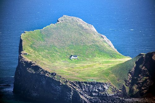 Lonely house on one of the isles of Vestmannaeyjar.    Shot through plane window.    Elliðaey, Vestmannaeyjar, Iceland