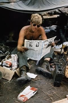 "THE VIETNAM WAR 1962 - 1975 part of ""UNITED STATES ARMY"" (photographs) Made by: United States Army official photographer An off-duty American soldier, PFC Mark Kramer, of 2 Bn, 8 Regt, 1 Air Cavalry Division, reads a copy of the US Department of Defense newspaper 'Pacific Stars and Stripes' at Fire Support Base Jay, 4 miles from the Cambodian border, 21 March 1970."
