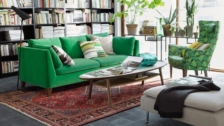 """Ein Wohnzimmer mit viel Grün, u. a. Mit STOCKHOLM 3er-Sofa mit Bezug """"Sandbacka"""" grün, STOCKHOLM Sessel mit hoher Rückenlehne mit Bezug """"Mosta"""" grün, STOCKHOLM Couchtisch in Nussbaumfurnier, BILLY Bücherregalen in Schwarzbraun, kurzflorigem PERSISK MIX Teppich und vielen Grünpflanzen"""
