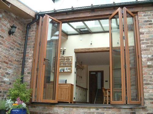 Desain eksterior rumah minimalis dengan jendela kaca besar, bingkai kayu dan bata ekspose