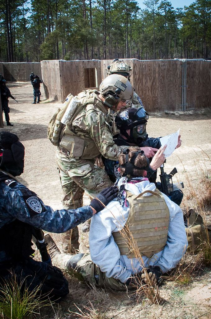 A Green Beret from the 7th Special Forces Group (Airborne) helps a Honduran TIGRES understand information on a document discovered while searching a detainee role-played by a soldier from the unit Feb. 27, 2015,.  Intelligence on the document led the TIGRES to a secondary objective, located at a separate range on Eglin Air Force Base.  The TIGRES, a counter-narcotic and counter-trafficking force, were participating in culmination exercise testing the nearly two weeks of advanced training…
