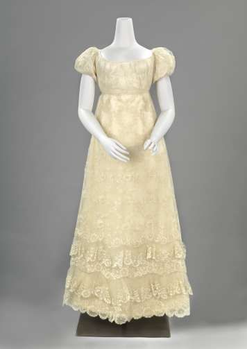 c.1815-20 Gown of silk lace, 'Blonde', in Empire style with low neckline and puffed sleeves. With a pattern of whorls of flowers and leaves. Rijksmuseum