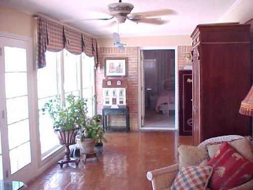 """Sunroom.  Entry to guest suite shown.  Also opens to """"5th bedroom"""" living room, and master suite.  Door has glass paneled windows."""