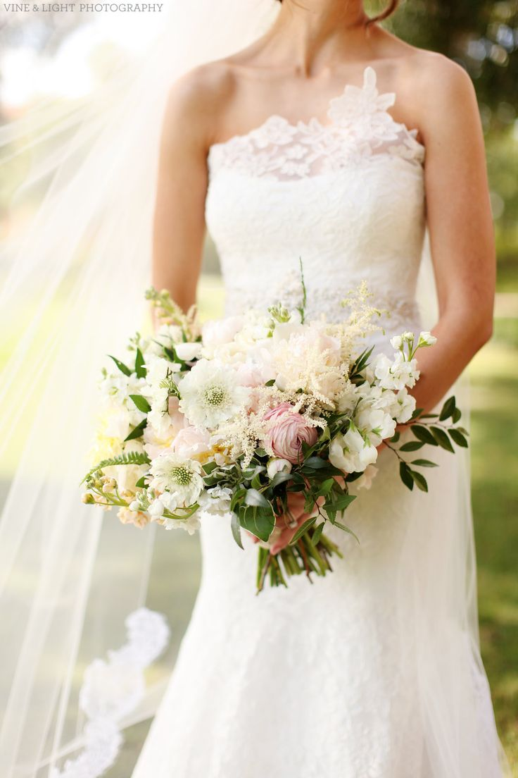 loose, organic bridal bouquet of  light pink peony, peach stock, white stock, white scabiosa, white astilbe, snow on the mountain, light pink ranunculus, white majolik spray rose, fern, elm & jasmine vine