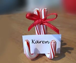 Candy Cane Placecard Holder ~~ So simple to do ... 3 candy canes glued together with a ribbon on top ... Love this idea . . .