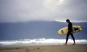 Surfer on Hell's Mouth beach near Abersoch, Wales