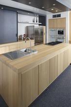 Moderne houten keuken met rvs accenten. Deze prachtige keuken straalt zowel warmte als professionaliteit uit. Door de aanwezigheid van de in rvs uitgevoerde apparaten ziet de keuken er professioneel uit. Neem alleen al de bijzondere vaatwasser die in het aanrechtblad ingebouwd wordt. Doordat er zowel voor het werkblad als voor de keukenkasten gekozen is voor dezelfde warme houtkleur krijgt de keuken een aangename warme uitstraling. De keuze voor een plafond afzuigsysteem zorgt ervoor dat de…