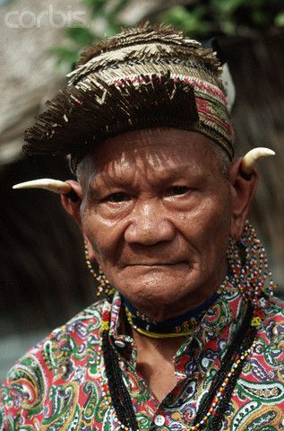 Indonesia ~ Borneo | An elderly Dayak man from the Orang Uli tribe wears bear claws in his ears | © Charles & Josette Lenars