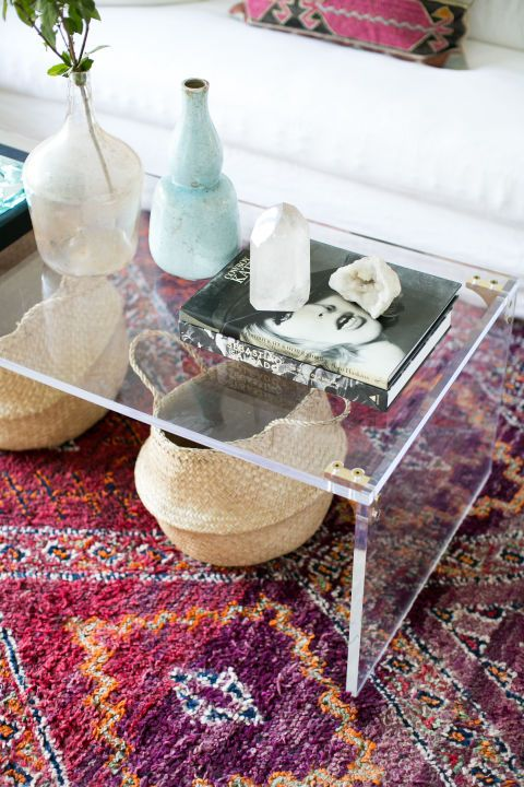 A clear coffee table lends this room a modern feel and puts both the rug and the storage baskets beneath it on display. Design by Ashley Clark via ruemag.com