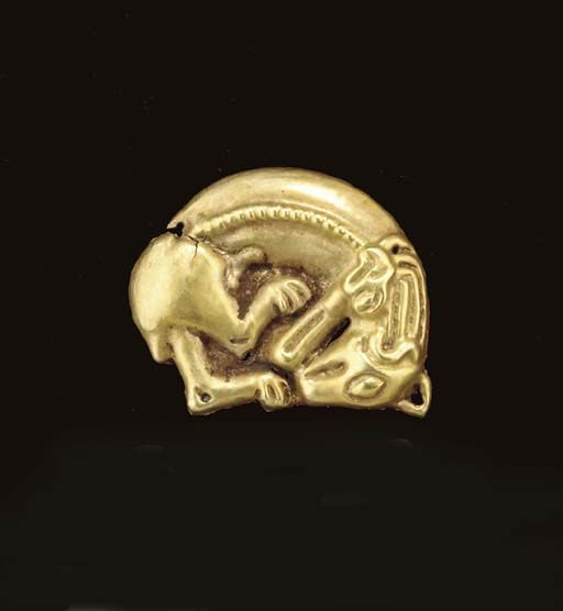 A SCYTHIAN GOLD APPLIQUÉ Circa Late 6th-Early 5th Century B.C. Die-formed, depicting a panther, its body coiled, an avian head at its shoulders, a band of beading along its back, the edges perforated for attachment
