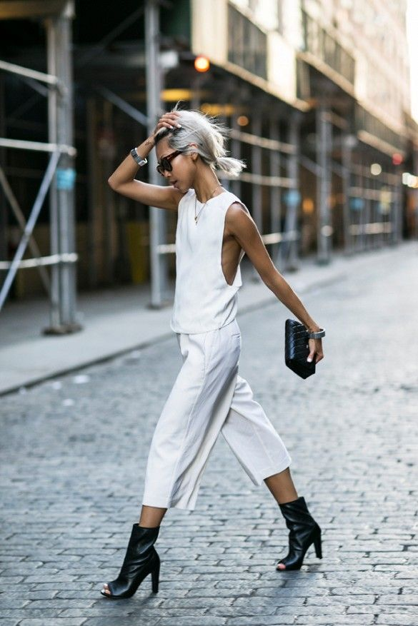 The Haute Pursuit wears a white tank top, cropped pants, peep-toe boots, a Chanel clutch, and sunglasses