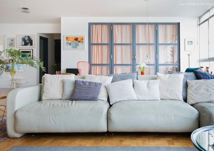 Sala com sofá cinza e almofadas no mesmo tom. Ao fundo, porta de ferro com…