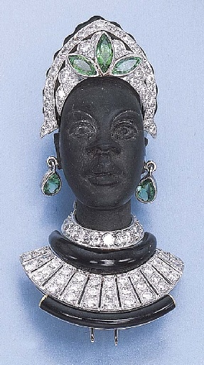 A BLACKAMOOR BROOCH  The black wooden bust of a woman wearing a diamond-set head ornament, necklace and collar, the head ornament with three marquise-cut emeralds, to the pear-shaped emerald ear pendants, mounted in platinum and 18k gold