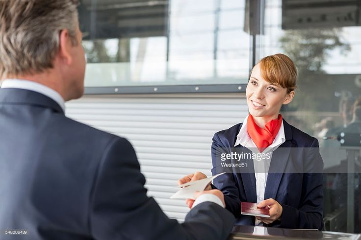Stock Photo : Airport check-in attendant handing out documents to passenger