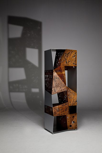 Design: Steven Holl, 2006 / After the first edition in walnut, since 2011, Riddled Totem is offered in ebony: the valuable dark wood confers further charm and elegance to the sculptural volumes, already characterized by the typical perforated texture of many famous works by Steven Holl. It consists of an aluminium frame and five elements made ​​of 2-mm wooden sheets folded in an origami-like fashion, thanks to a complex and patented technological process.