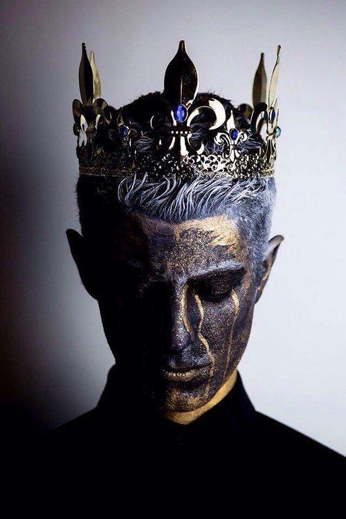 Um rei arruinado: alguma rachaduras no rosto para dar um efeito de estátua.  Segurando com as duas mãos proxima ao seu rosto, um crânio com um contorno espectral de asas de libélula