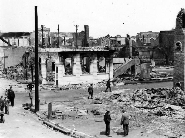 The photograph shows the corner of Browning and Hastings streets, Napier after 3 February 1931 earthquake and subsequent fire. The destroyed Bank of New Zealand building can be seen on the corner. All that remains of it are the exterior walls. Surrounding the bank are the ruins of shops. The old Napier Post Office chimney can be seen on the right of the photograph.  Photographer, Cyril Walter Lambourne. Date, post 3 February 1931.