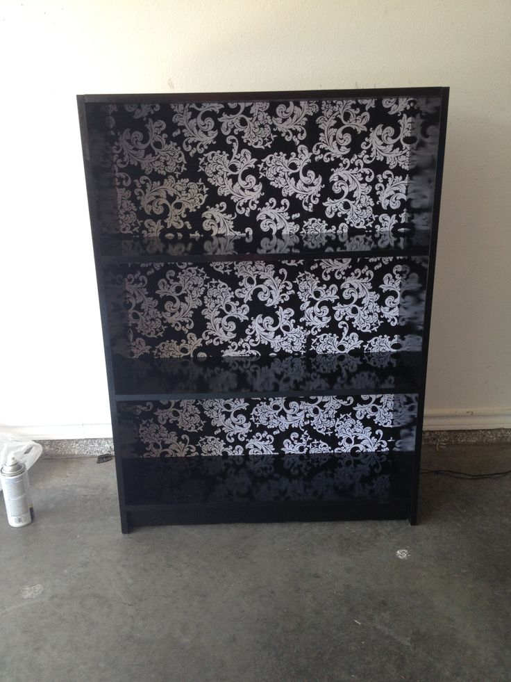 Old particle board bookcase with a fresh coat of glossy black spray paint and fabric covered backboard (held together with duck tape because it was broken