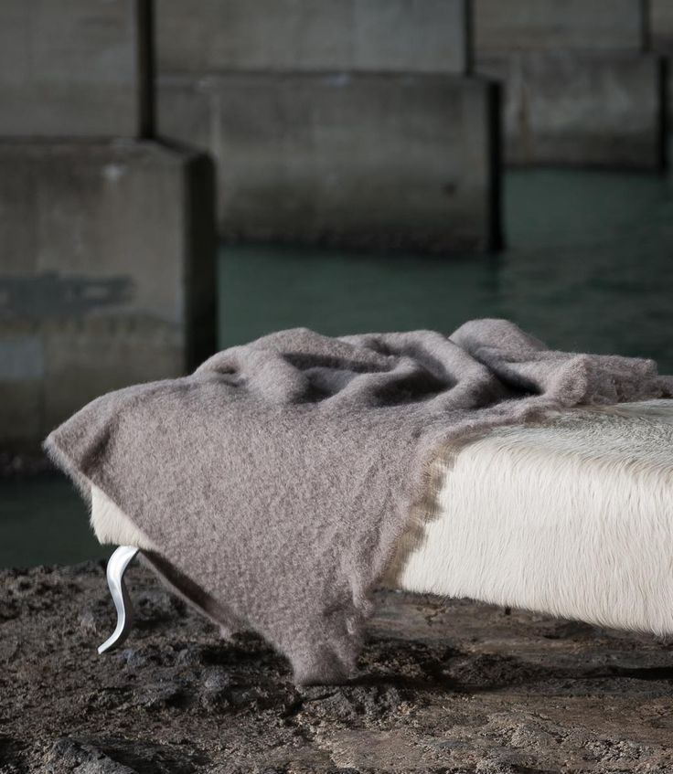 A classic taupe mohair throw on an off-white cowhide ottoman both from Gorgeous Creatures.