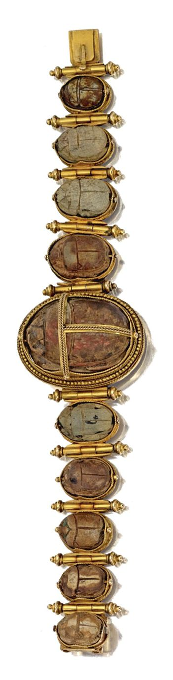 ARCHAEOLOGICAL-REVIVAL GOLD AND HARDSTONE SCARAB BRACELET, CIRCA 1870.  Composed of 10 hardstone scarabs, the reverses engraved with hieroglyphs, within gold rope and beadwork frames, separated by gold batons with bead terminals, length 7 inches.