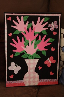 Valentine- Scrapbook paper and a poster frame. Showcasing kid's handprints as the flowers.