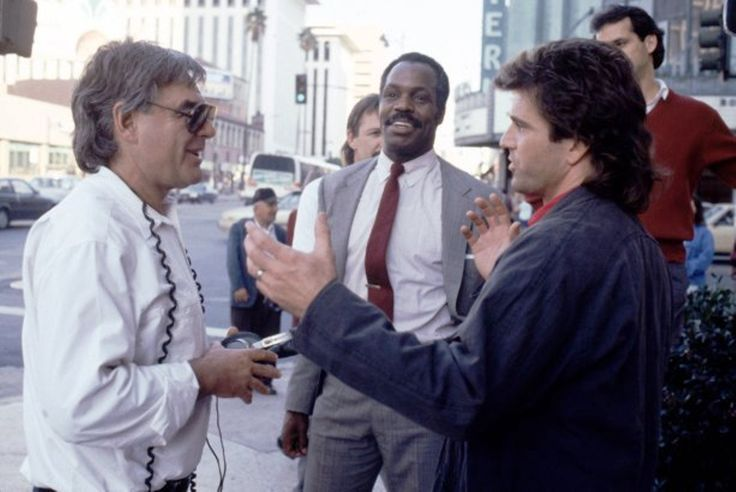 "Director Richard Donner (left) talks with Danny Glover (center) and Mel Gibson (right) on the set of ""Lethal Weapon 2"", 1989."