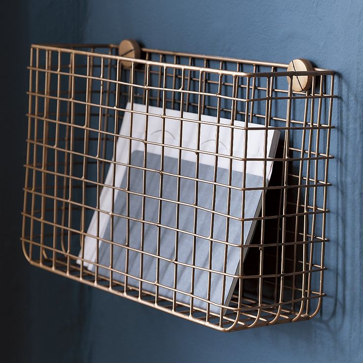 Wall-mounted grid copper magazine storage from CB2. To hold homework