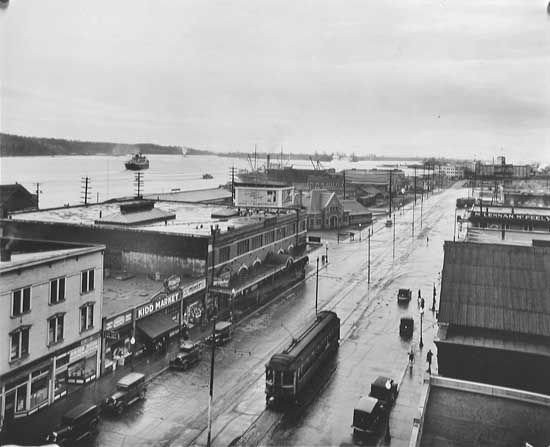 Photograph shows a view from Westminster Trust block looking west along Columbia street to the foot of Tenth Street. Store fronts shown are; Fraser Café, K.K. Reid for Mayor office, Tip Top Taylor, Kidd Market, Overwaitea, McKenzie's , BC Electric Station, CPR Station, McLennan, McFeely, and Prior. Good view of Columbia Street, to Tenth, Old Columbia Street, and river front buildings. Ships steaming and tied at dock, car traffic and street cars are running. 1932.  IHP7791