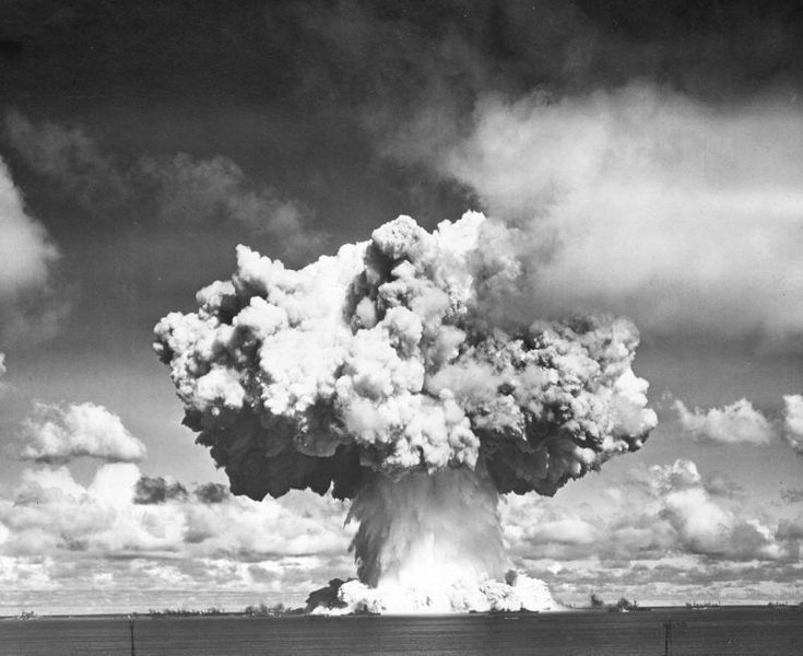 Operation Crossroads. The Wilson cloud evaporated revealing the cauliflower atop the spray column. Two million tons of water spray fall back into the lagoon. The radioactive base surge is moving toward the ships.