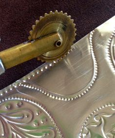 Use stencils for embossing!! MercArt: The Metal Embosser: Stencils and Aluminum on a Tin Box