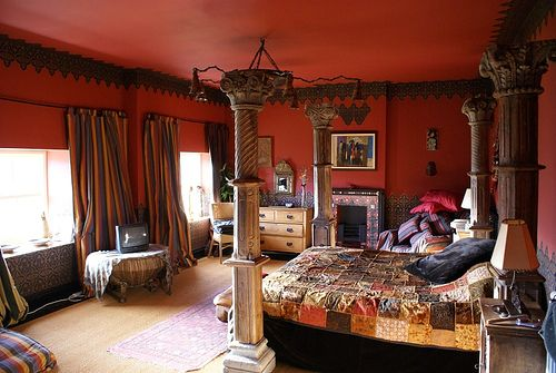https://www.flickr.com/photos/miketd/2083838325   This bedroom includes columns, shades of red, and detailed patterns that are all commonly found in Moroccan design. The detailed carving of the pillars are another key trait to be noted. Moroccan design often consists of details in architecture.
